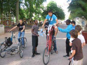Plusieurs jeunes personnes autour d'un tall-bike et autres vélos bizarres