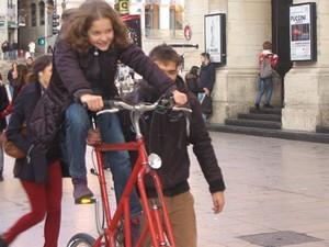 Jeune personne sur un tall-bike rouge, se faisant assurée par un-e adulte
